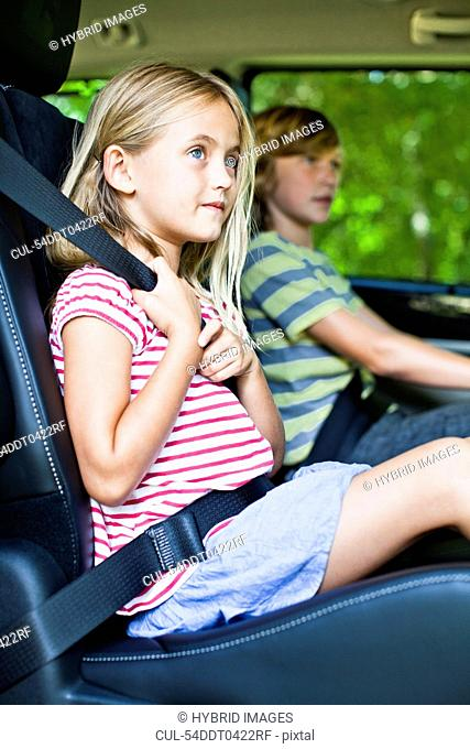 Girl sitting in car booster seat