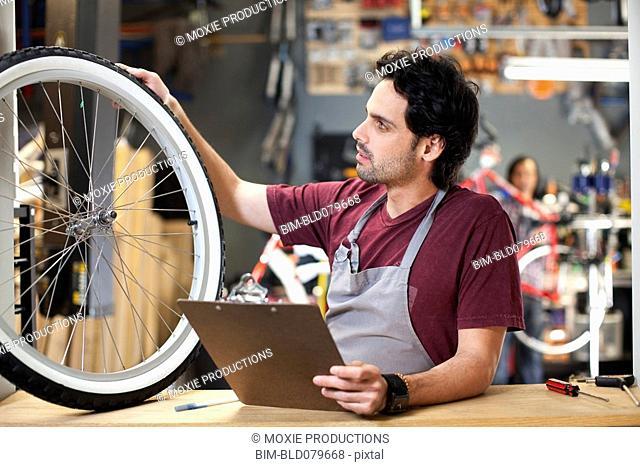 Hispanic bike shop owner examining bicycle tire