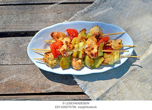 Lunch grilled chicken and vegetable skewers. White plate on a checkered green tablecloth