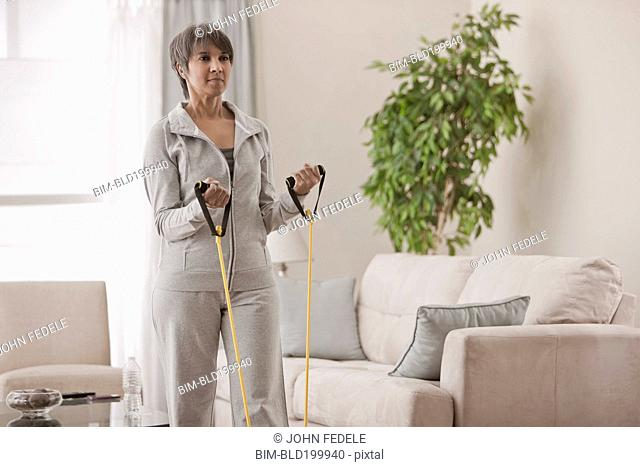 Mixed race woman exercising in living room