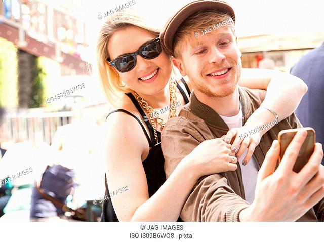 Young couple, outdoors, taking selfie, using smartphone