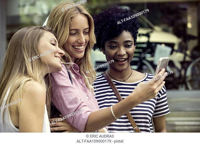 Friends using smartphone to take a selfie