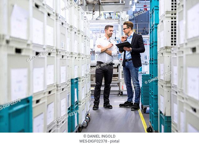 Two men with tablet talking at boxes in factory shop floor