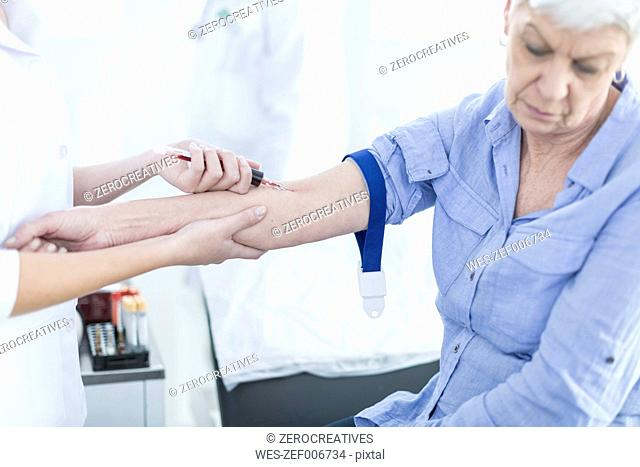 Nurse taking blood from patient, close up
