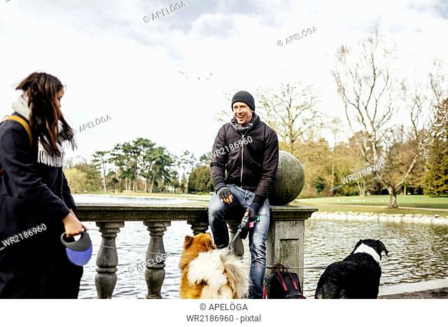 Couple with dogs standing on bridge by lake at park