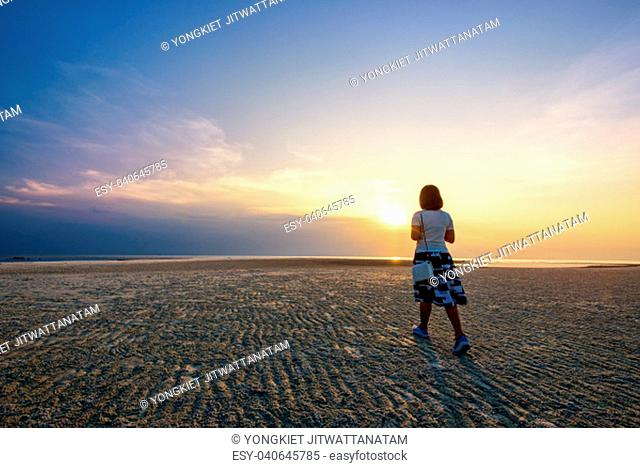 Young woman tourist strolling on the beach watching the beautiful natural landscape, colorful of the sky and the sea during a sunset at Nathon Sunset Viewpoint...