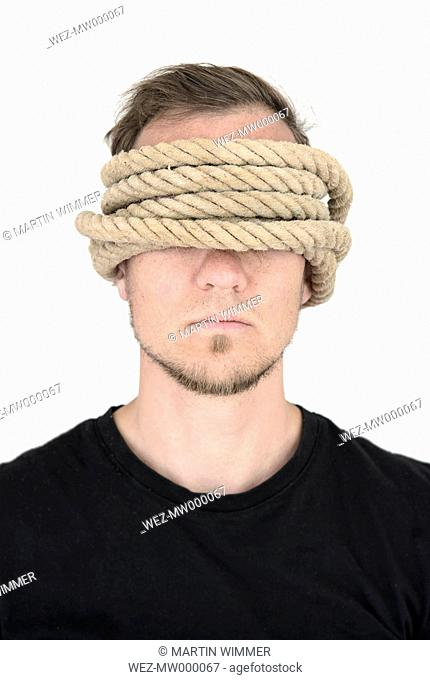 Man with covering eyes and ears, rope