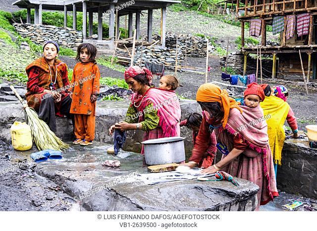 Women with children doing laundry. Malana village, Himachal Pradesh, India
