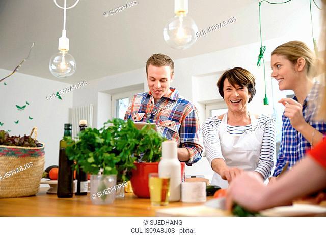Mother with grown up children preparing food in kitchen