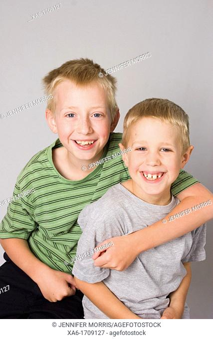 A pair of young blond haired boys, brothers, against a grey background