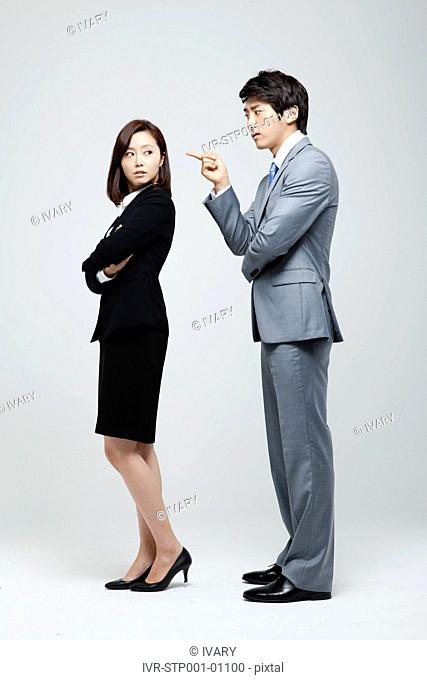Asian Businessman Pointing Toward Businesswoman