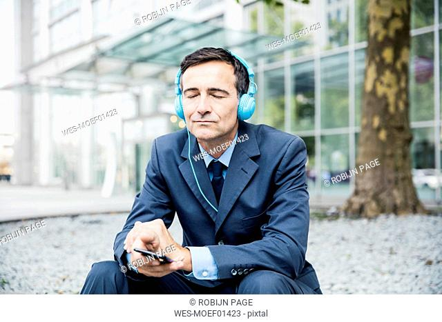 Businessman with closed eyes listening to music with headphones in the city