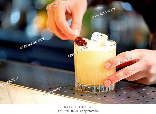 alcohol drinks, people and luxury concept - bartender adding cherry into glass and preparing cocktail at bar