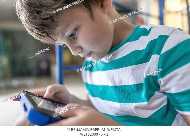 concentrated young boy using mobile device for digital education