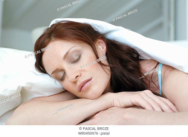Close-up of a mid adult woman sleeping on the bed