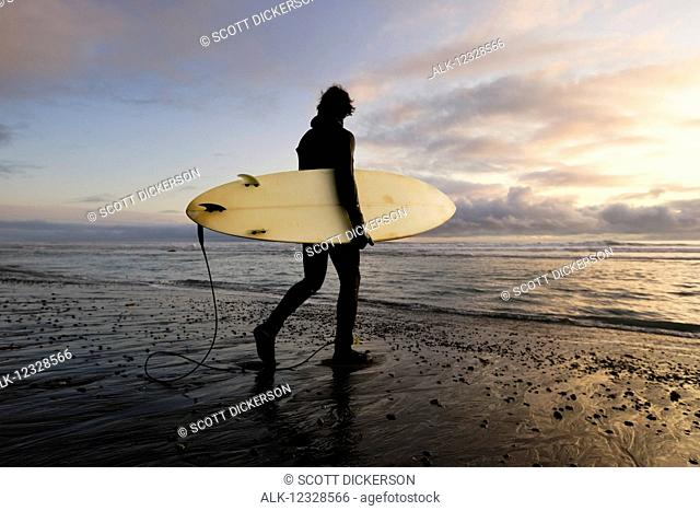 Surfer with board at sunset, Southeast Alaska; Yakutat, Alaska, United States of America