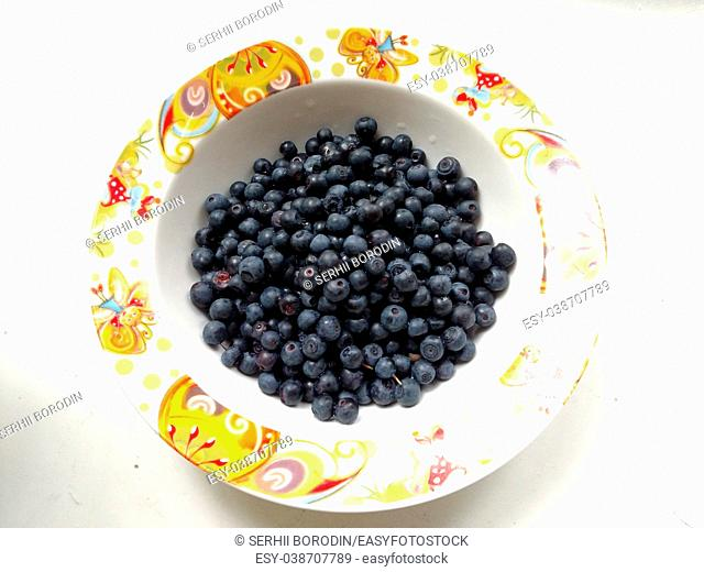 Fresh bilberry in the plate on white background. Concept for healthy eating and nutrition. Rustic style. Vitamins for breakfast