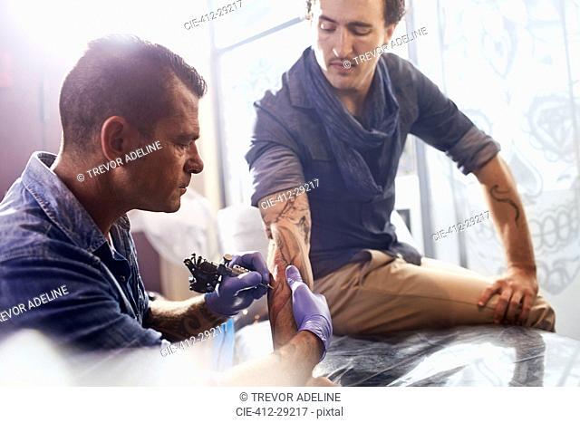 Tattoo artist tattooing man's forearm