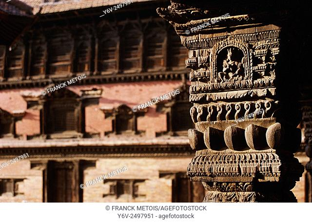 Wooden pillar representing a hindu goddess. In the background, the former royal palace. Durbar square at Patan ( Nepal)