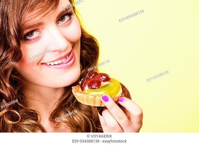 Sweetness and happiness concept. Closeup cute funny woman eating fruit cake cupcake having fun sticking tongue yellow background