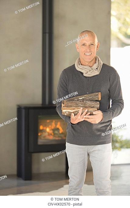 Portrait smiling mature man holding firewood in front of wood burning fireplace