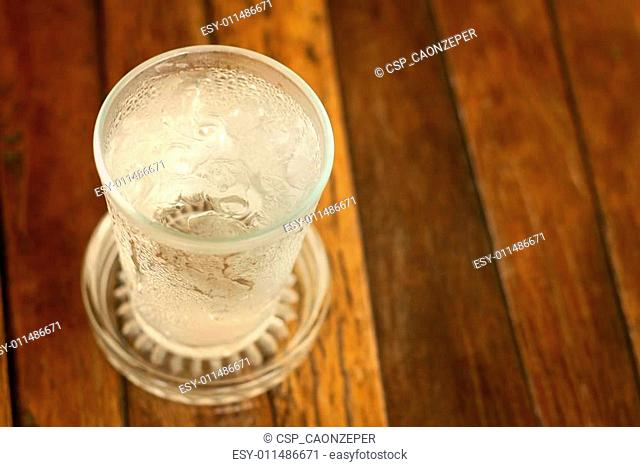 Water in a glass on a background of brown wood