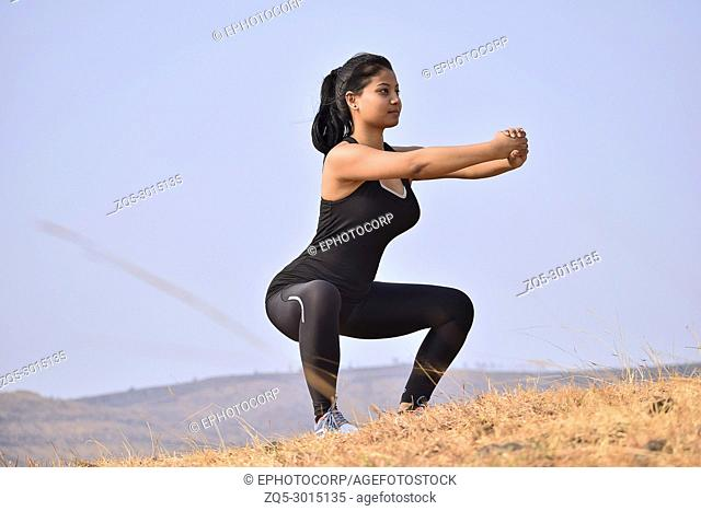 Young Indian girl doing fitness squat exercise. Mountain backdrop, Pune, Maharashtra