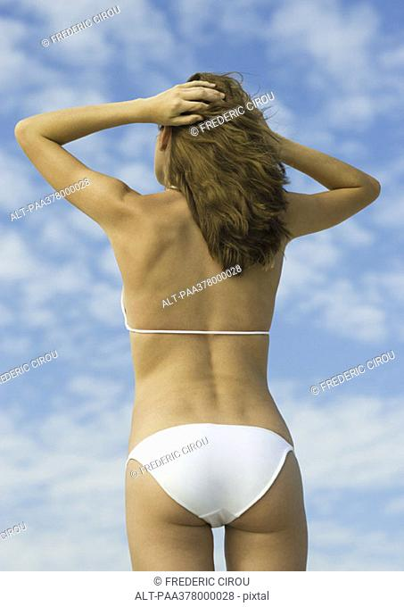 Woman in bikini standing with hands in hair, low angle rear view