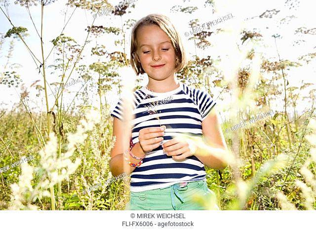 Girl Picking Flowers in Field, Poland