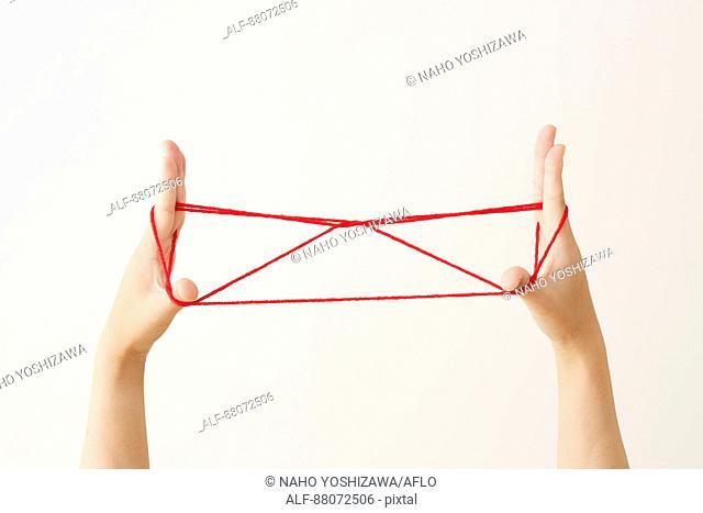 Japanese woman playing with red string