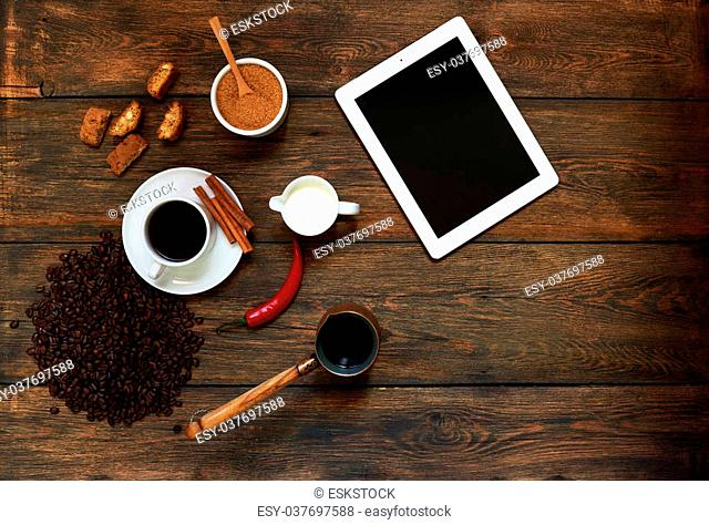 An example of the coffee in a coffee shop or restaurant, on a vintage table is a cup of strong coffee next to milk, a famous French pastry