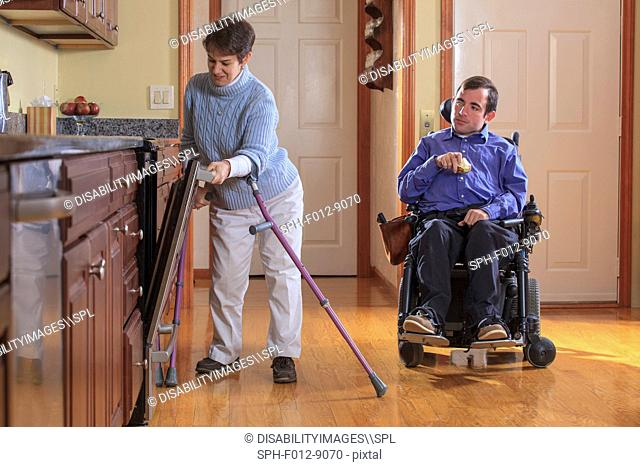 Man and woman with Cerebral Palsy preparing for lunch and using the dishwasher in their home kitchen