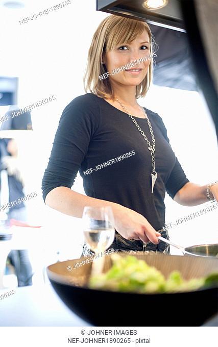 Smiling young woman preparing food