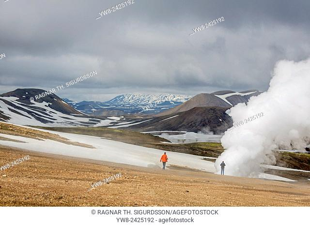 Tourist by steaming fields, geothermal area, near Hrafntinnusker, Landmannalaugar, Central Highlands, Iceland