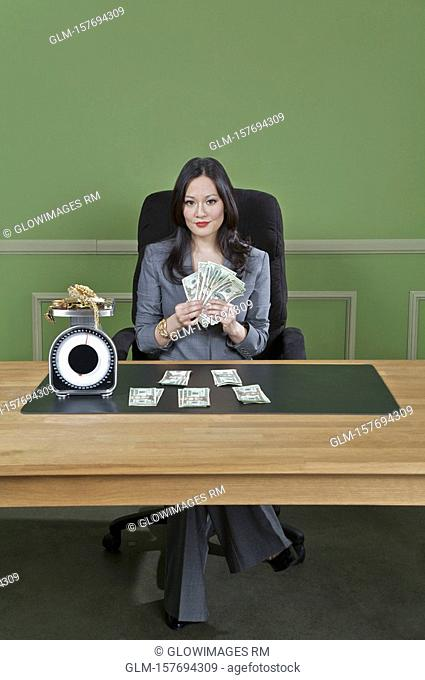 Businesswoman holding currency notes with gold jewelry on a weight scale in front of her