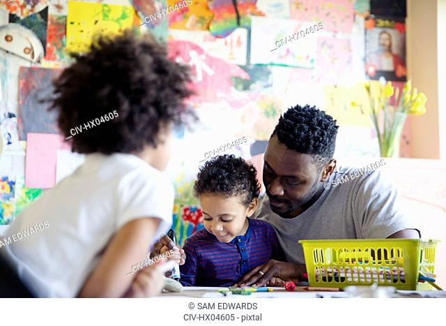 Father and toddler children coloring at table