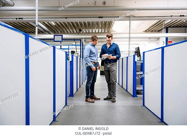 Factory managers looking at digital tablet in factory corridor