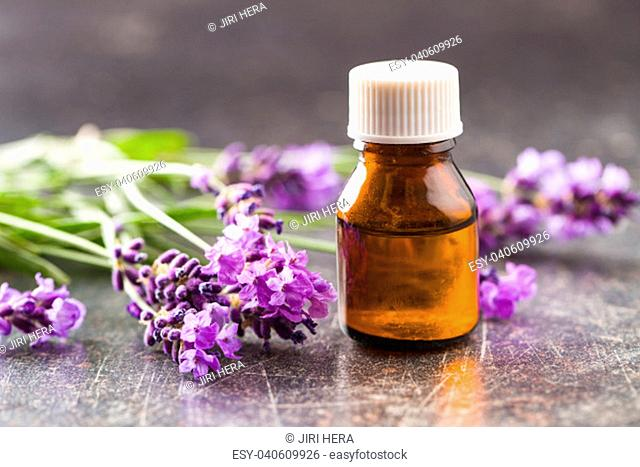 Essential oil and lavender flowers on old table