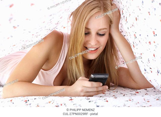 Women under blanket with cellphone
