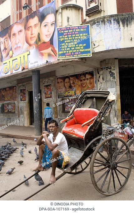 Hand Rickshaw Puller sitting in his Rickshaw on street waiting for passenger ; Kolkata  ; West Bengal ; India
