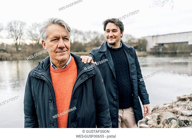 Confident senior man and young man standing at the riverside