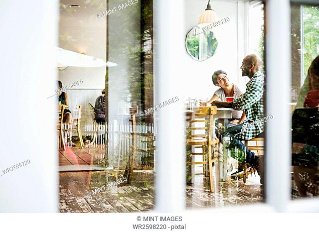 View through a window into a cafe, people sitting at tables