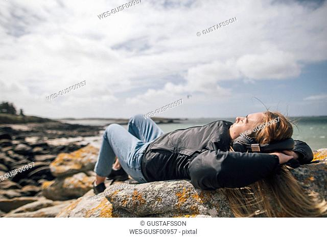 France, Brittany, Landeda, young woman wearing headphones lying at the coast
