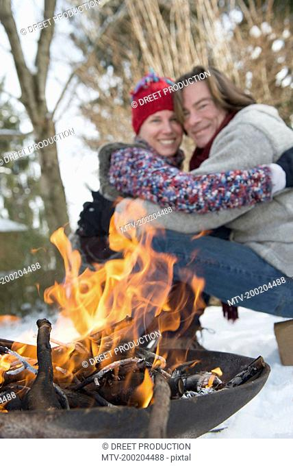 Couple sitting by fire in winter, smiling, Bavaria, Germany
