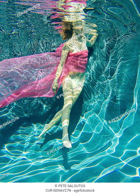 Woman draped in fabric swimming semi-naked underwater