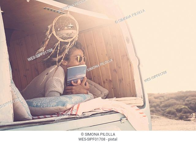 Spain, Tenerife, woman with book in parked van at twilight