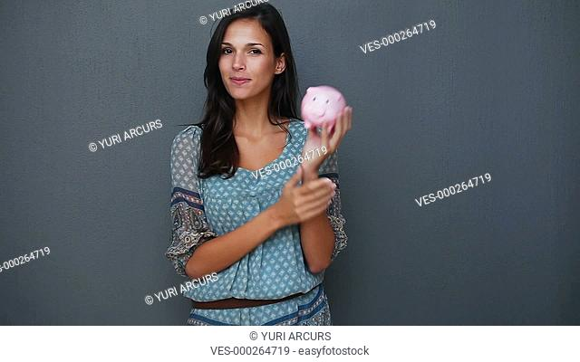 Cute young woman holding a piggybank and smiling while isolated on a blue background