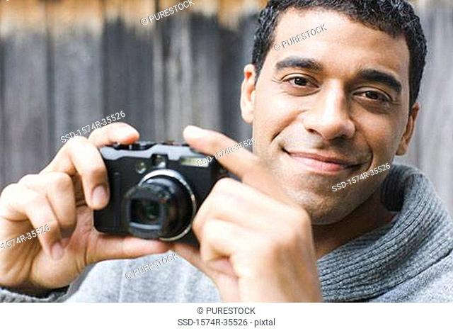 Portrait of a man holding a camera