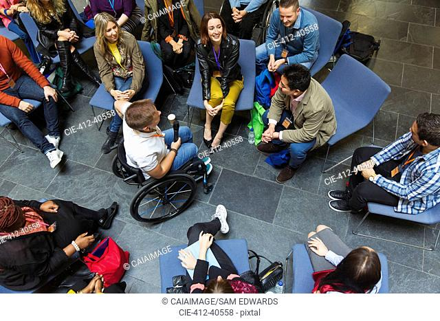 Overhead view speaker in wheelchair with microphone talking with audience