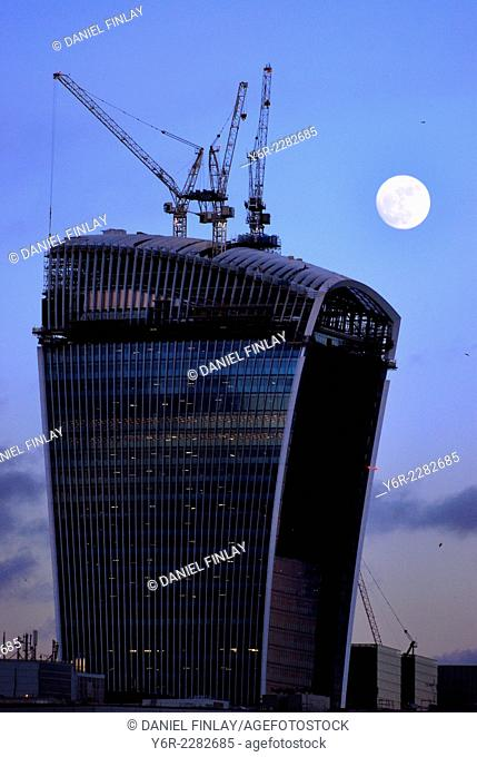 Building iwork n City of London international business district, England, seen at night against full-moon